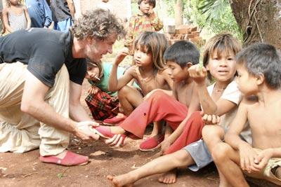 "TOMS founder, Blake Mycoskie, participating in a ""shoe drop."""